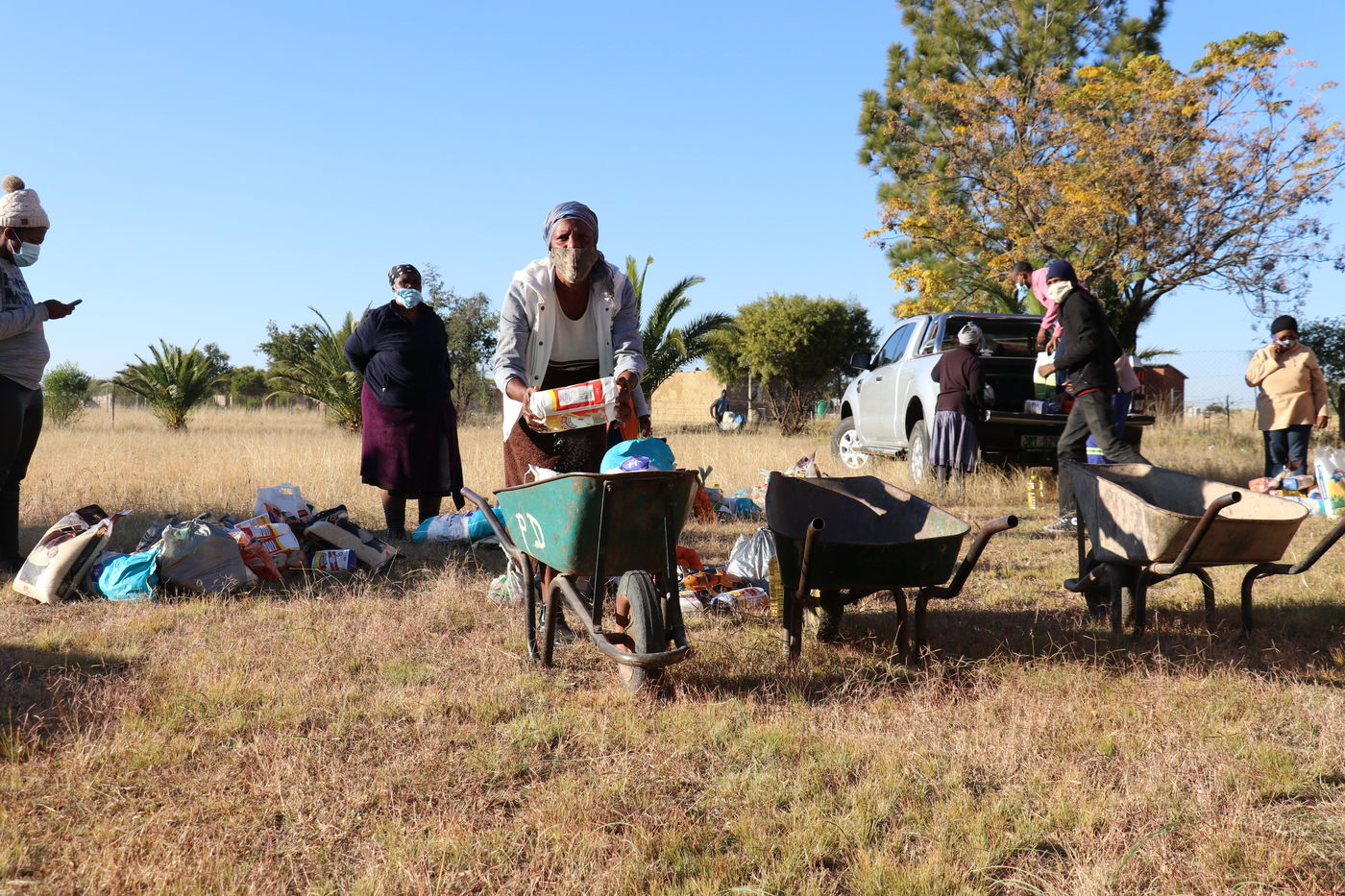 Loading a wheelbarrow at an E1 F1 food distribution at Bodibe