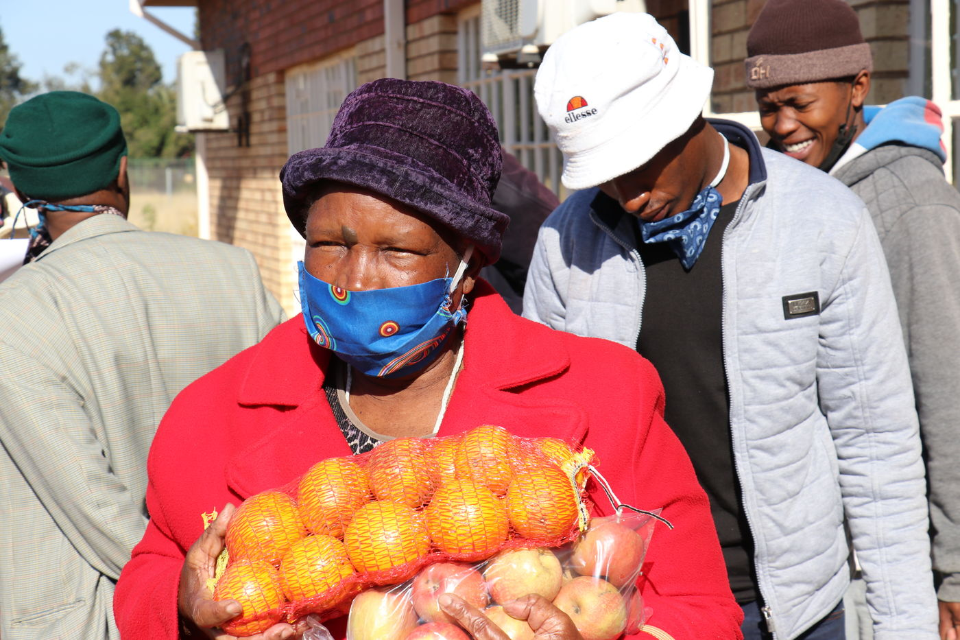 A woman receives oranges at an E1 F1 food distribution at Bodibe