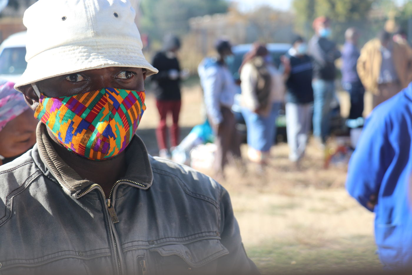 A man in a mask at an E1 F1 food distribution at Bodibe