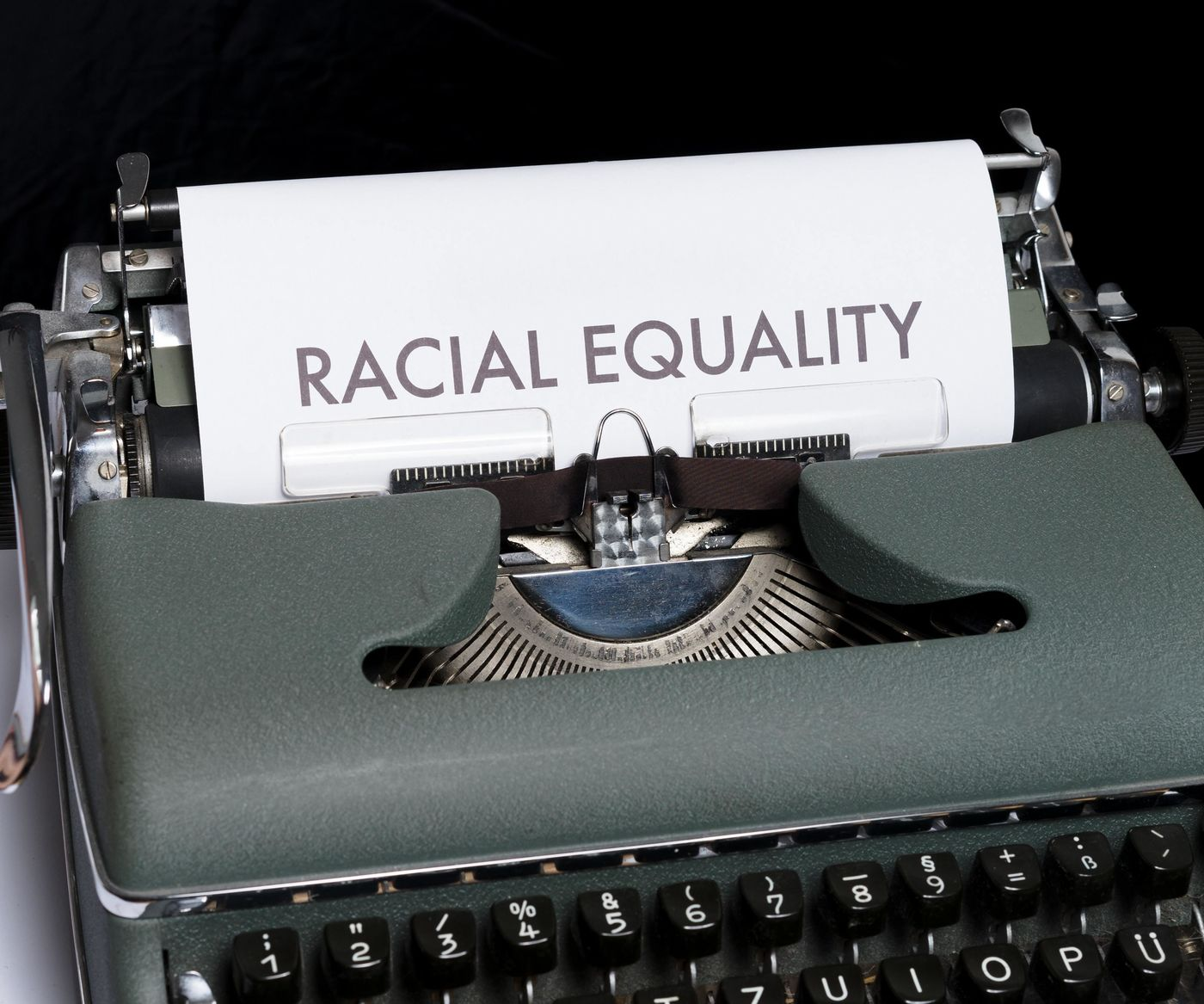 "typewriter and ""racial equality"" typed on a sheet of paper"